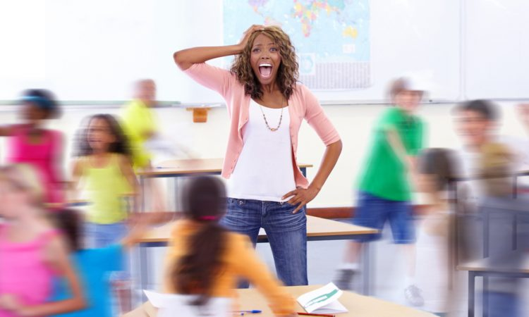 Portrait of a young teacher shouting as her students run around her